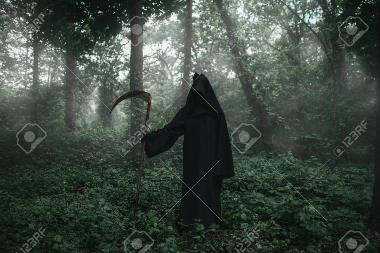 Death In A Black Hoodie With A Scythe In Forest Stock Photo, Picture And  Royalty Free Image. Image 105135689.